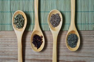 various herbs in wooden spoons