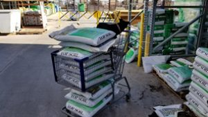 shopping cart filled with bags of soil