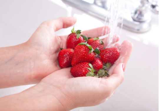 person washing strawberries