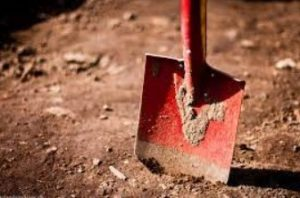 red shovel digging into brown dirt